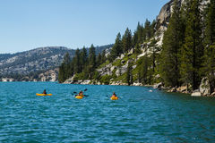 Tre kayakers på Echo Lake i Sierra Nevada berg, Kalifornien, USA Royaltyfri Fotografi