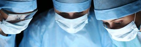 Tre kirurger på arbete som fungerar i kirurgisk teater Fotografering för Bildbyråer