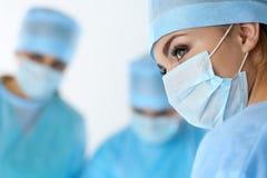 Tre kirurger på arbete som fungerar i kirurgisk teaterbesparingpati Royaltyfria Foton