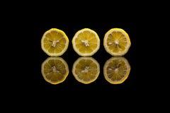 Tre klippta citroner på svart bakgrund Arkivfoto