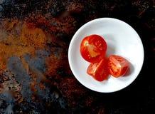 Tre klippte röda tomater i en vit bunke, rätt av mitten, brun bakgrund arkivfoto