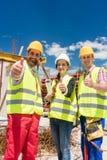 Tre kollegor i ett konstruktionslag som visar tummar upp under arbete arkivbilder