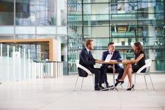 Tre kollegor på ett möte i foajén av en stora affärer arkivbilder
