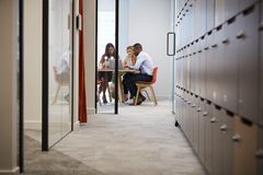 Tre kollegor som använder bärbar datordatoren på ett kontorsmöte royaltyfri foto