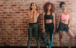 Tre konditionkvinnor som står mot tegelstenväggen Royaltyfri Foto