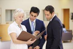 Tre konsulenter som diskuterar patientanmärkningar i sjukhus royaltyfria foton