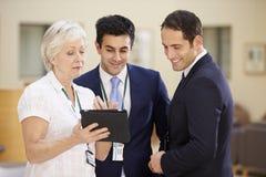 Tre konsulenter som diskuterar patientanmärkningar i sjukhus royaltyfria bilder