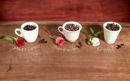 Tre koppar som är fulla av kaffebönor med rosor Arkivfoto
