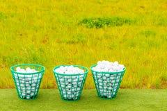 Tre korgar som fylls med golfbollar på gräset Arkivfoton