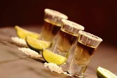 Tre korta exponeringsglas med alkohol bredvid en skiva av limefrukt och salt är på en gammal lantlig tabell med tappningtextur Arkivbild