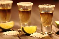 Tre korta exponeringsglas med alkohol bredvid en skiva av limefrukt och salt är på en gammal lantlig tabell med tappningtextur Arkivbilder