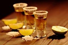 Tre korta exponeringsglas med alkohol bredvid en skiva av limefrukt och salt är på en gammal lantlig tabell med tappningtextur Royaltyfri Foto