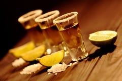 Tre korta exponeringsglas med alkohol bredvid en skiva av limefrukt och salt är på en gammal lantlig tabell med tappningtextur Royaltyfri Bild