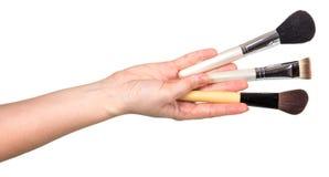 Tre kosmetiska borstar i den kvinnliga handen som isoleras på den vita backgrouen Arkivbilder