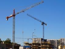 Tre kranar på arbete Sikt av huskonstruktionsplatsen royaltyfri fotografi