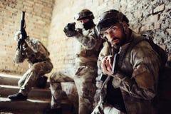 Tre krigare står på trappa och att posera Mannen i en framdel ser det rättframa och hållande vapnet Andra Arkivbilder