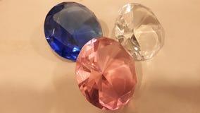 Tre kristaller skimrar i str?larna av ljus arkivbild