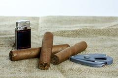 Tre kubanska cigarrer med en skärare och en tändare Fotografering för Bildbyråer