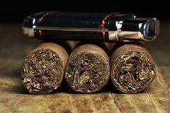 Tre kubanska cigarrer med en tändare Arkivbild