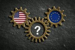 Tre kugghjul kritiserar på bakgrund med flaggorna av USA och EU och enfläck i mitt royaltyfri bild
