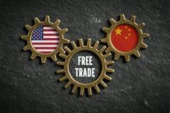 Tre kugghjul kritiserar på bakgrund med flaggorna av USA och Kina och orden 'frihandel ', royaltyfria bilder