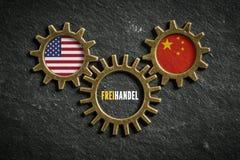 Tre kugghjul kritiserar på bakgrund med flaggorna av USA och Kina och ordet 'frihandel 'i tyskt fotografering för bildbyråer