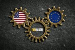 Tre kugghjul med flaggorna av USA och EU och ordet 'frihandel 'i tysk i mitt royaltyfria bilder