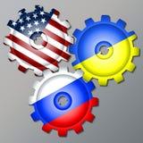 Tre kugghjulhjul som målas i färgerna av flaggan av Ryssland, Ukraina och USA Royaltyfria Foton