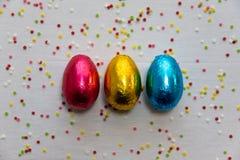 Tre kul?ra chokladeaster ?gg p? vit bakgrund och f?rgrika konfettier arkivfoto