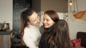Tre kvinnavänner kramar tillsammans att hälsa Vänligt möte i kafé arkivfilmer