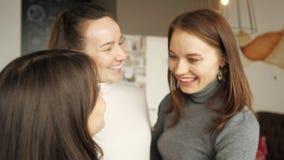 Tre kvinnavänner kramar tillsammans att hälsa Vänligt möte i kafé lager videofilmer