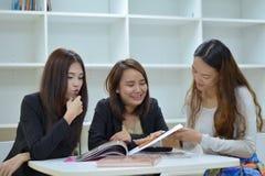 Tre kvinnavänner läste tidskriften Royaltyfri Foto