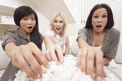 Tre kvinnavänner som äter hållande ögonen på film för Popcorn Fotografering för Bildbyråer