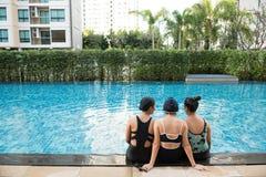 Tre kvinnavänner som har gyckel tillsammans i simbassängtogethe arkivbilder