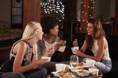 Tre kvinnliga vänner hänger ut att äta ett kinesiskt tagande-bort arkivbild