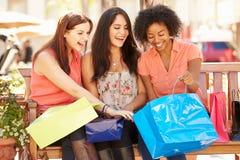 Tre kvinnliga vänner med shoppingpåsar som sitter i galleria Arkivfoton