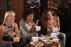 Tre kvinnliga vänner som äter en hållande ögonen på TV för kinesiskt tagande-bort arkivbilder