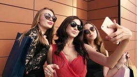 Tre kvinnliga vänner som poserar för ett foto mot orange bakgrund stock video