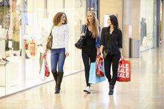 Tre kvinnliga vänner som tillsammans shoppar i galleria Royaltyfria Foton