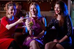 Tre kvinnliga vänner som tycker om att dricka Royaltyfria Bilder