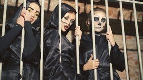 Tre kvinnliga vampyrer som skrämmer och flörtar i gallren av katakomben i 4K arkivfilmer