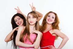 Tre kvinnligvänner på vit bakgrund Fotografering för Bildbyråer