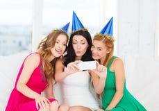 Tre kvinnor i hattar som har gyckel med kameran Arkivfoto