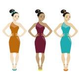 Tre kvinnor i klänningar på vit bakgrund Royaltyfria Foton