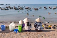 Tre kvinnor i koniska hattar i fiskeläge. Mui Ne. Vietnam Royaltyfri Bild