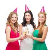 Tre kvinnor i rosa hattar med champagneexponeringsglas Arkivbild