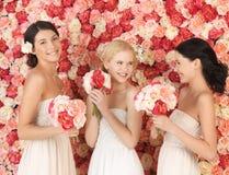 Tre kvinnor med bakgrund som är full av rosor Fotografering för Bildbyråer