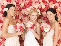 Tre kvinnor med bakgrund som är full av rosor Royaltyfria Foton
