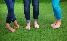 Tre kvinnor med naken fot som står i gräs Royaltyfri Fotografi