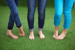 Tre kvinnor med naken fot som står i gräs Arkivfoton